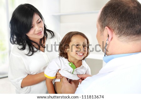 doctor examining heartbeat of the cute kid with stethoscope - stock photo