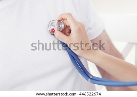 Doctor examining heartbeat with stethoscope, close-up view