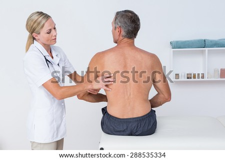 Doctor examining her patient arm in medical office - stock photo