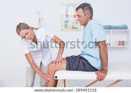 Doctor examining her patient knee in medical office - stock photo