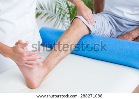 Doctor examining her patient leg in medical office - stock photo
