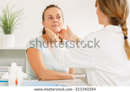 Doctor examining her patients glands at the doctors office - stock photo