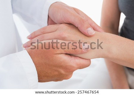 Doctor examining his patient hand in medical office - stock photo