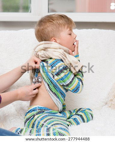 doctor examining little boy with stethoscope - stock photo