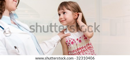 Doctor examining little girl.  Room for text - stock photo