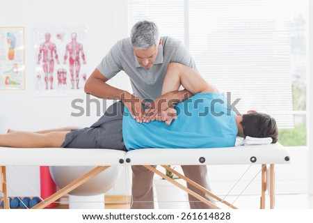 Doctor examining man back in medical office - stock photo