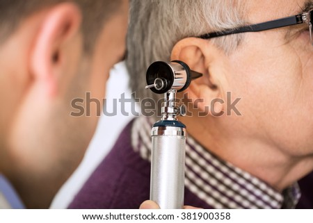 Doctor Examining old Patient's Ear - stock photo