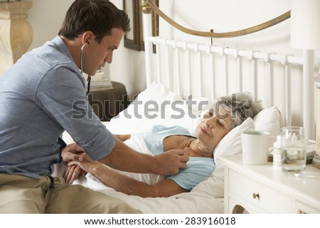 Doctor Examining Senior Female Patient In Bed At Home - stock photo