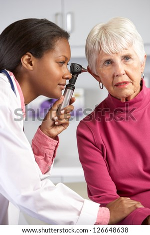 Doctor Examining Senior Female Patient's Ears - stock photo