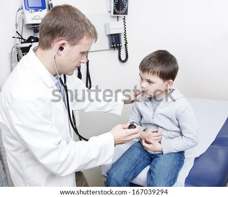Doctor Examining sick little boy - stock photo
