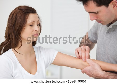 Doctor examining the arm of a patient in a room