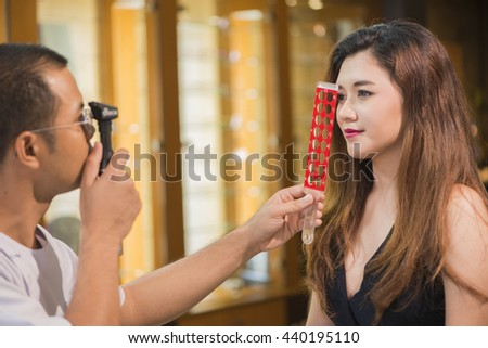 doctor examining woman's eyes with a measurement machine. (ophthalmologist) - stock photo
