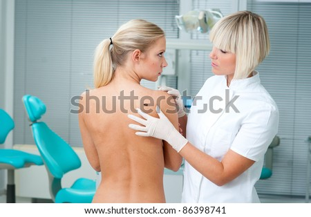 doctor examining woman skin for melanoma - stock photo
