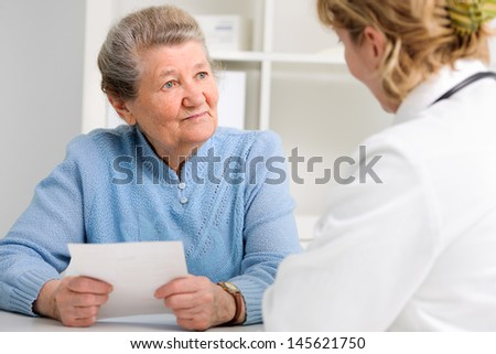 doctor explaining diagnosis to her female patient - stock photo