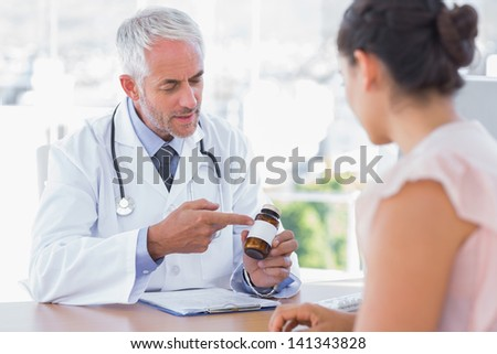 Doctor explaining the bottle of pills to patient in the office at desk - stock photo