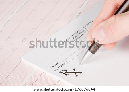 Doctor filling in empty medical prescription on electrocardiogram (ECG) chart