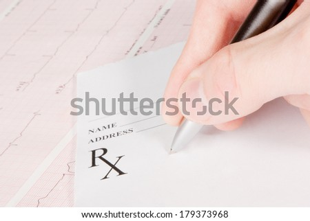 Doctor filling in empty medical prescription on electrocardiogram (ECG) chart - stock photo