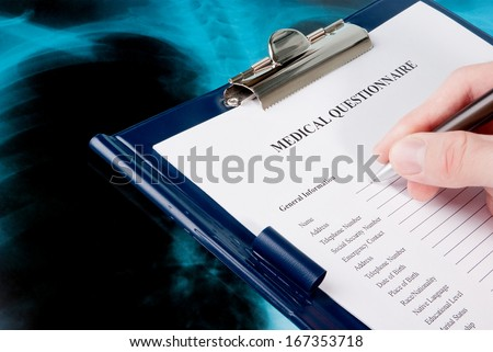 Doctor filling in medical questionnaire form in a clipboard on Xray photo of lungs - stock photo