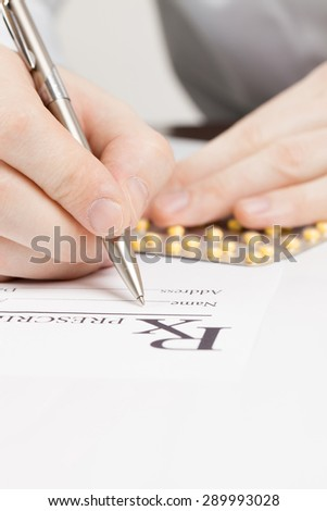 Doctor filling out drug prescription - close up shot - stock photo