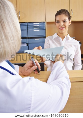 Doctor getting medical records in hospital from the receptionist - stock photo