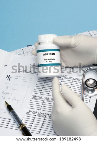 Doctor gives patient low dose aspirin with patient chart, electrocardiograph and stethoscope. - stock photo