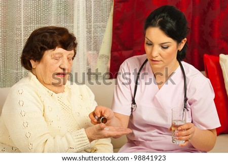 Doctor gives pills and water to senior woman patient in her home