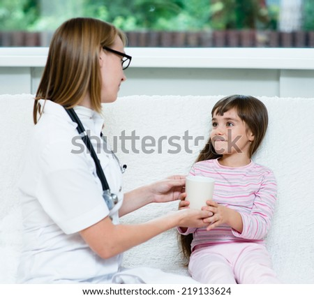 doctor gives to drink to the sick child - stock photo
