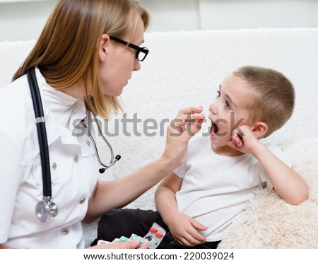 doctor giving a child a pill