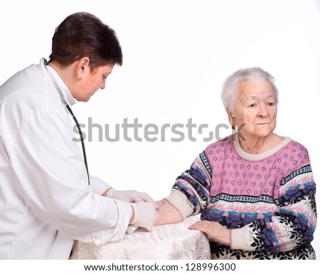 Doctor giving injection to old woman on a white background