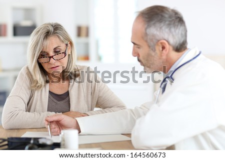 Doctor giving medicine to senior woman for arthritis pain