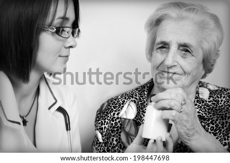 Doctor giving medicines and explaining how to take pills to elderly woman at home  - stock photo