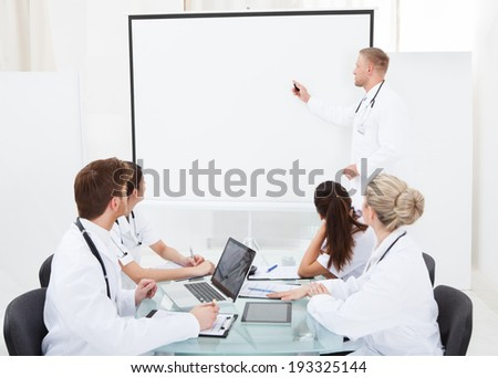 Doctor giving presentation to colleagues in meeting at hospital - stock photo