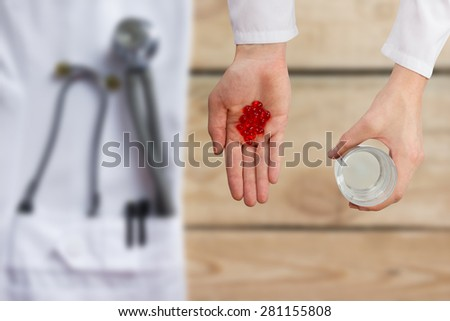 Doctor giving red pills and glass of water, hands close up with desktop on background, top view - stock photo