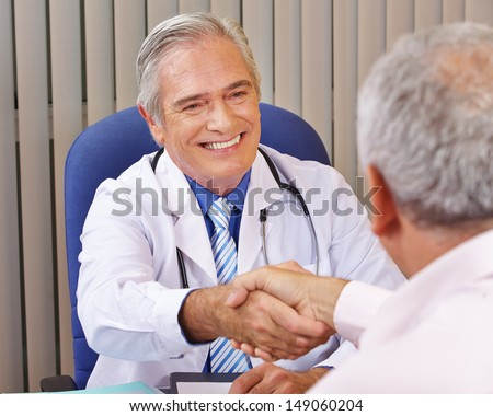 Doctor giving welcome handshake to patient in his office - stock photo