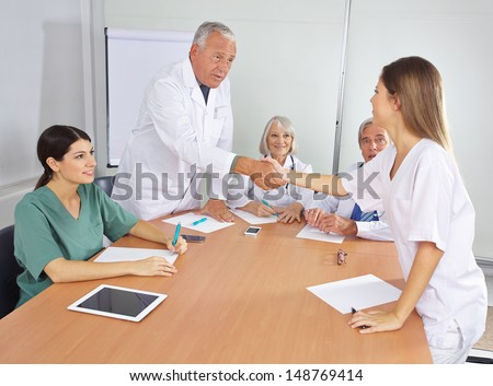 Doctor greeting new colleague in team with handshake - stock photo