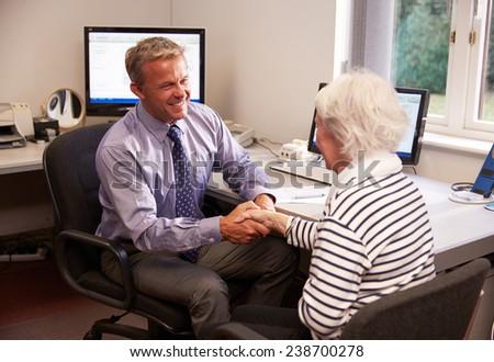 Doctor Greeting Senior Female Patient With Handshake - stock photo