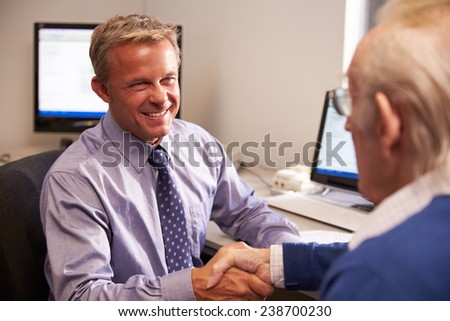 Doctor Greeting Senior Male Patient With Handshake - stock photo