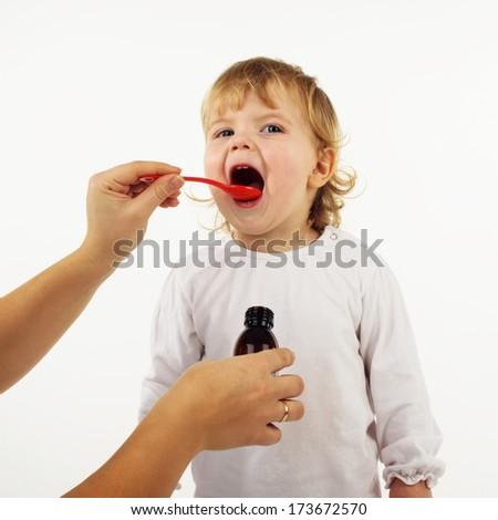 Doctor hand giving spoon dose of medicine liquid drinking syrup to child