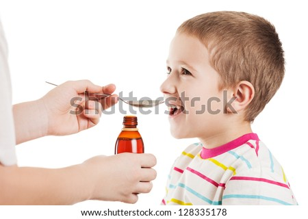 Doctor hand giving spoon dose of medicine liquid drinking syrup to child boy patient - stock photo