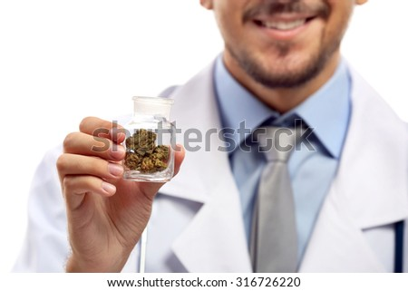 Doctor hand holding bottle with medical cannabis close up - stock photo
