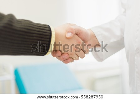 Doctor hand shaking with man in hospital