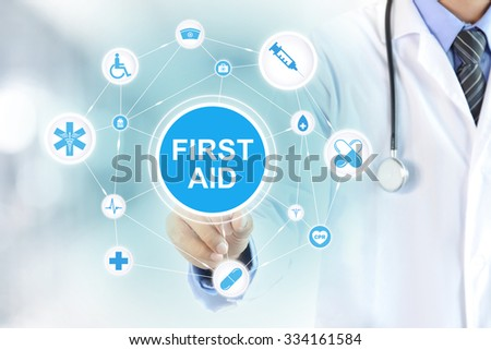Doctor hand touching FIRST AID words on virtual screen - stock photo