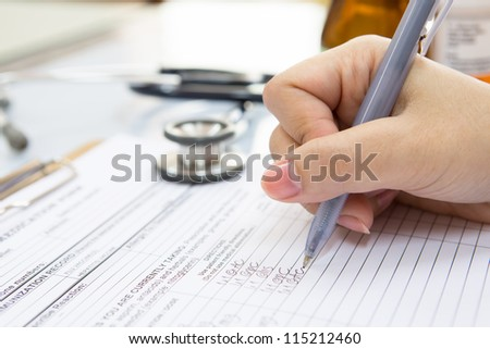 Doctor hand writing a medical recipe - stock photo