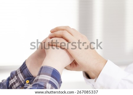 Doctor hands comforting his female patient