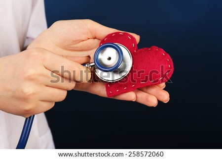 Doctor hands with heart and stethoscope on blue background