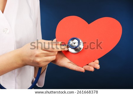 Doctor hands with heart and stethoscope on blue background - stock photo