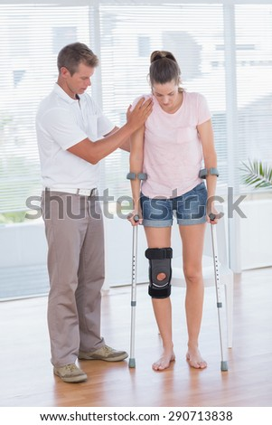 Doctor helping his patient walking with crutch in medical office - stock photo