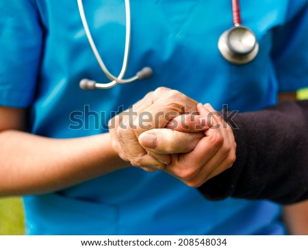 Doctor helping old patient with Alzheimer's disease. - stock photo