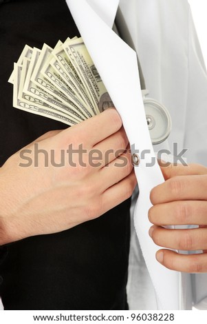 Doctor hiding money into his pocket. Corruption concept - stock photo