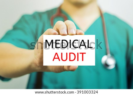 Doctor holding a  business card with capital lettering MEDICAL AUDIT in hand,Doctor shows card.Medical and healthcare  concept, medical support and service concept, Selective focus.vintage tone. - stock photo